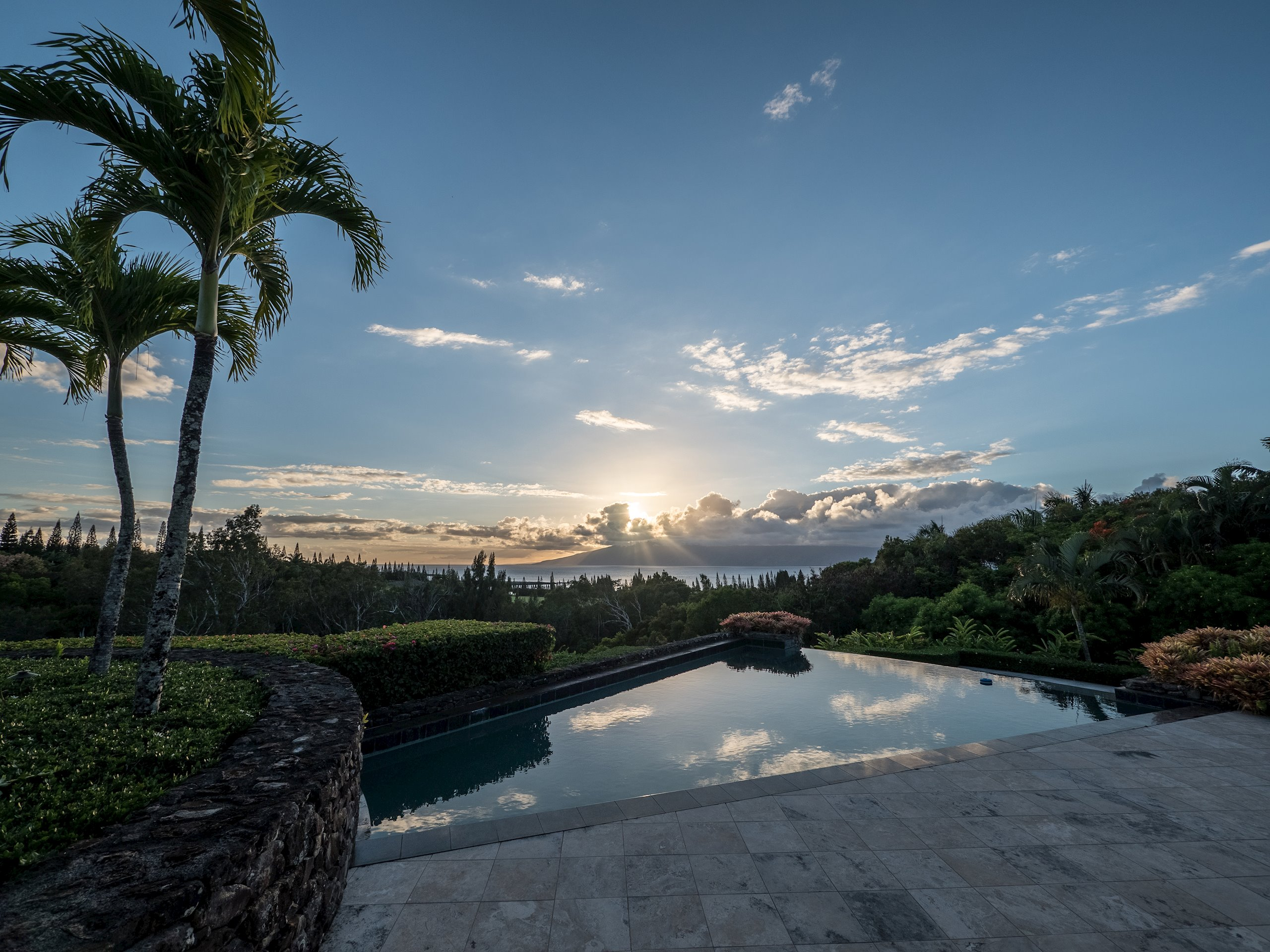 An exclusive estate with a 4,090 sq.ft. 3 bed/3.5 bath home and a 762 sq.ft. 2 Bed/2 Bath guest quarters. Situated on approximately 2.5 acres of lush, tropical landscaped agricultural land at the end of Plantation Club Drive in Kapalua. This quiet and secluded retreat has two luxurious master suites, gourmet kitchen, great room and office. Additional features include a hand-laid rock fireplace and feature walls, workout room, porte cochère and 3 car garage. Fabulous indoor/outdoor living with unique pool, spa and expansive outdoor entertainment area with covered barbecue area and fireplace. Enjoy exceptional views of sunsets over the azure Pacific Ocean while entertaining friends and family. This spectacular property has a commanding view the beautiful island of Molokai. It overlooks the emerald fairways of the PGA championship Plantation Golf Course and is currently owned by a celebrity golfer.
