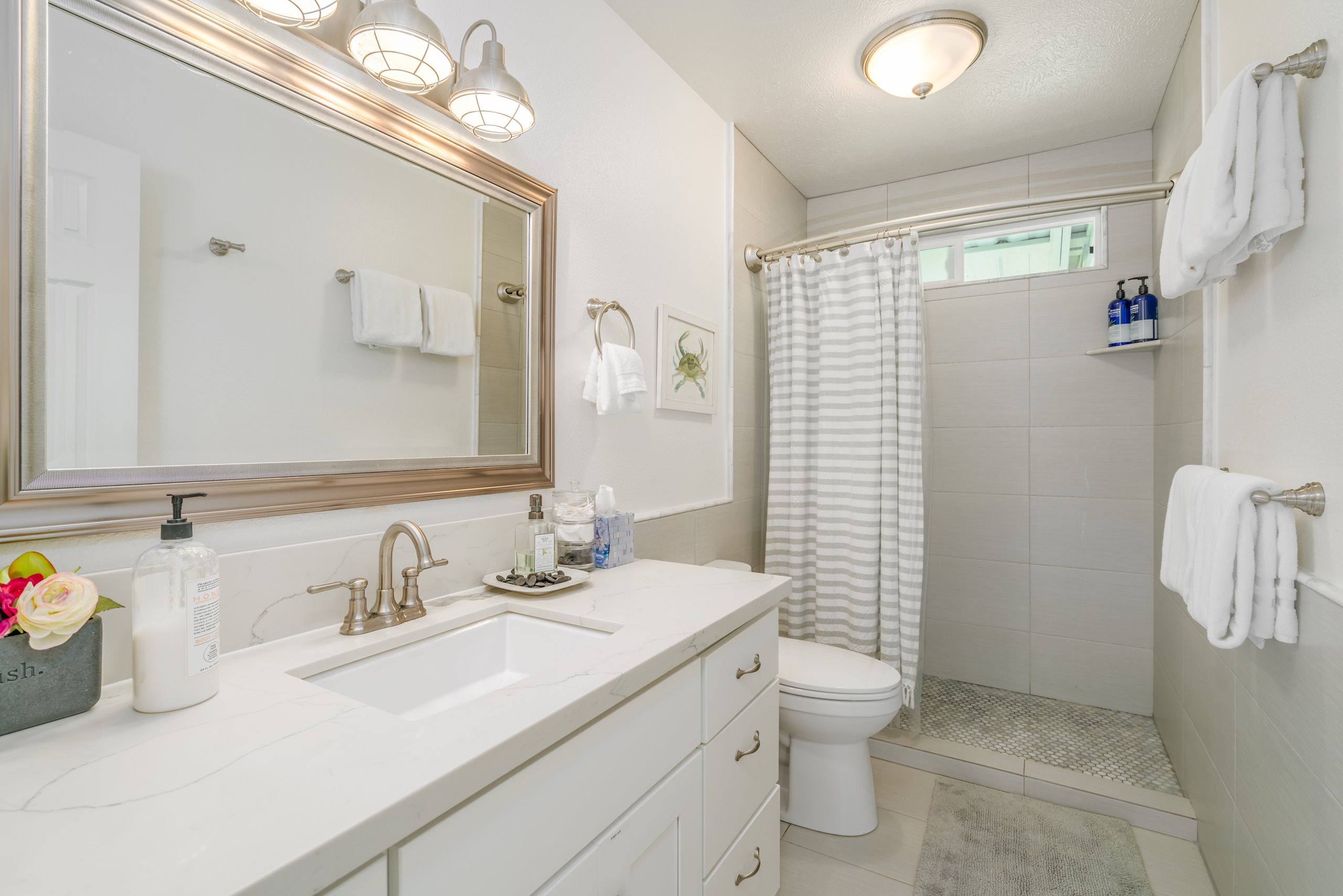 The upstairs guest bathroom with custom tile work, quartz countertops and high-end fixtures
