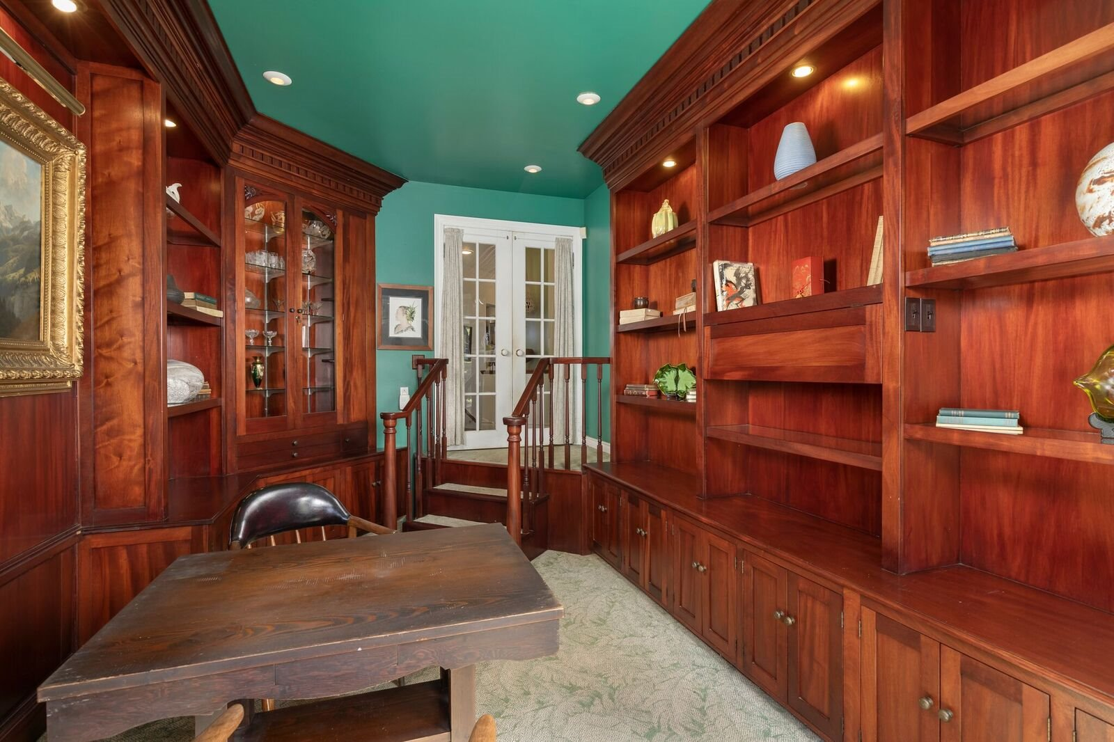 The office feels more like a library with wood and glass shelving throughout.