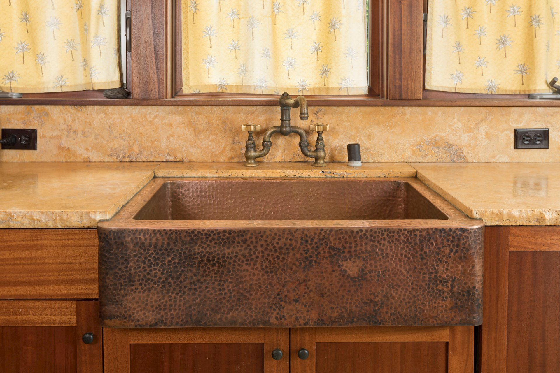 Hammered copper sinks throughout the home pair beautifully with the Sienna Peruvian travertine.