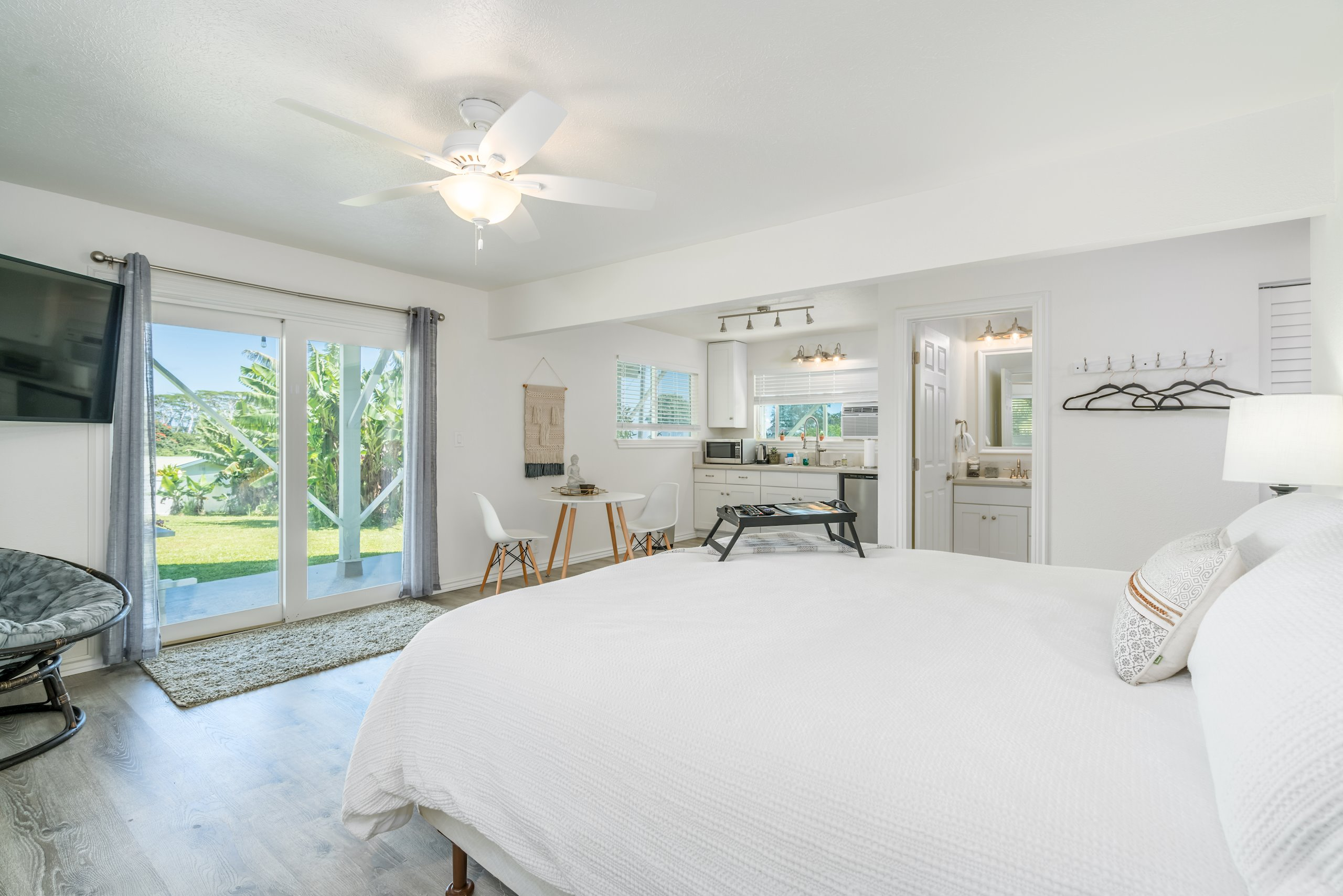 The downstairs master bedroom, with half kitchen and sliding doors that lead out into yard