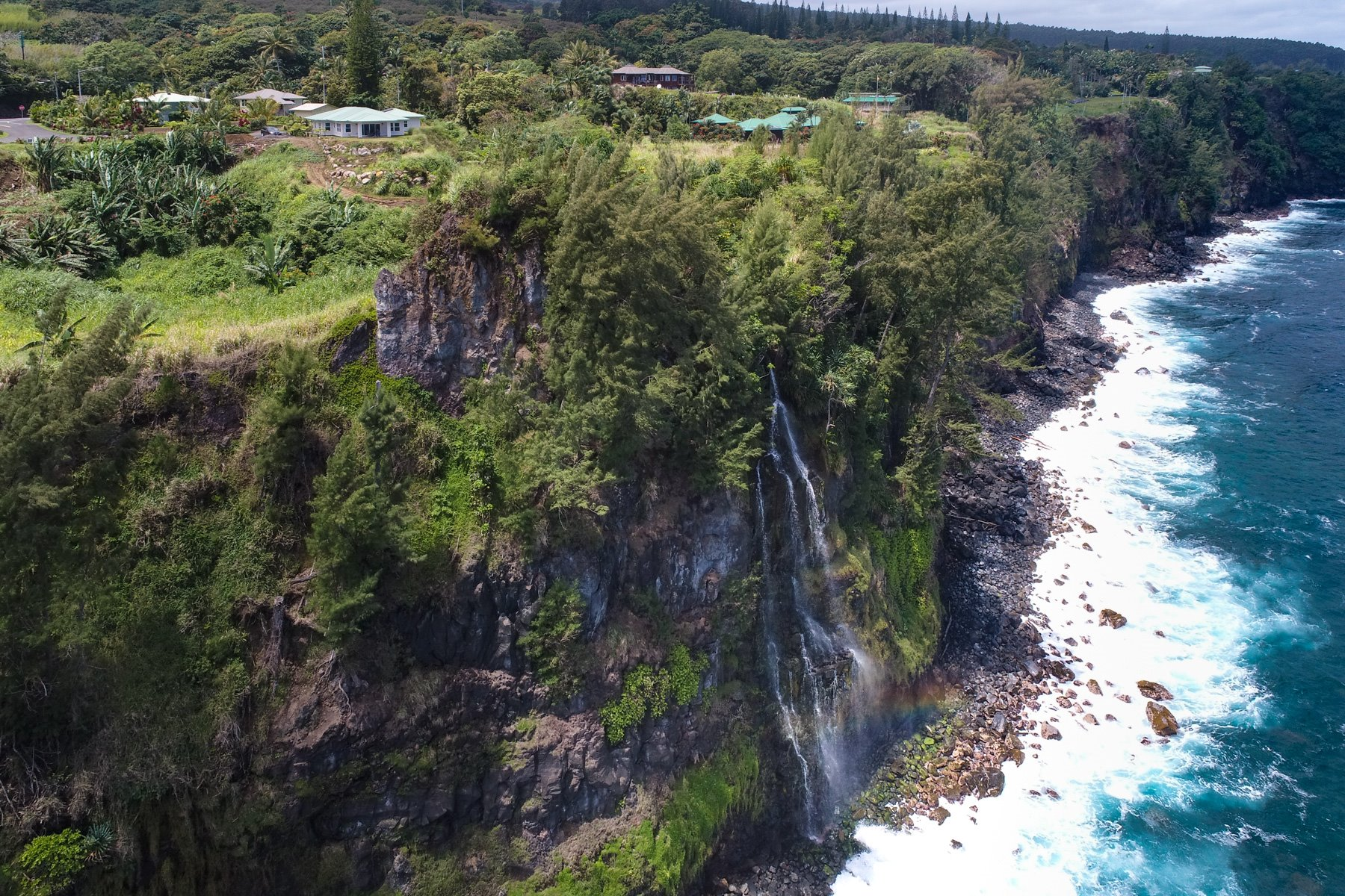 The stream turns into a waterfall when exiting into the ocean. Check out that rainbow at the bottom. Ninole is a majestic place!