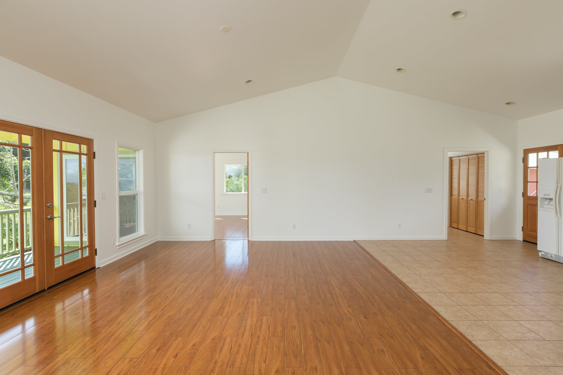 Light filled living room of the Yellow Twin. The Red Twin is identical. Hardwood as well as tiled flooring, high ceilings. The double glass doors to the left lead to the lanai and look to the tree farm