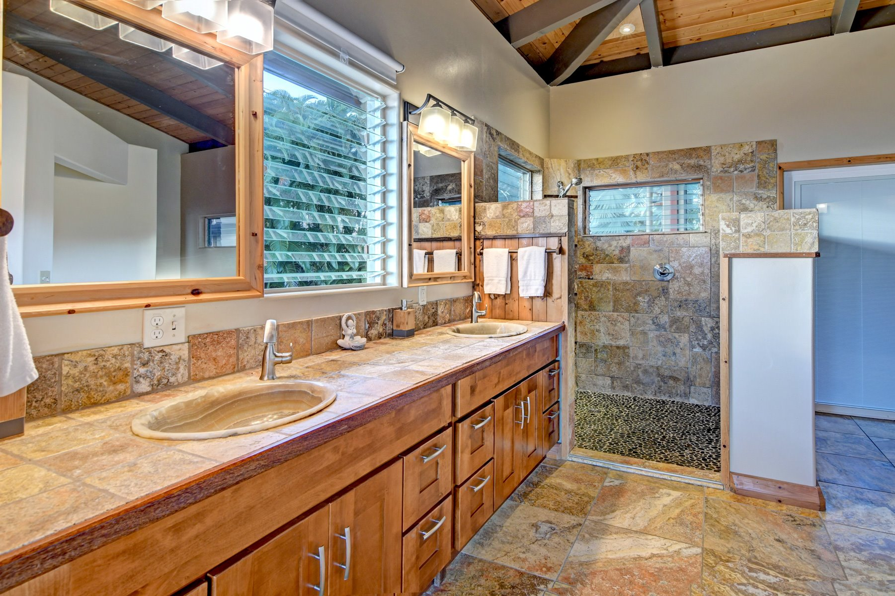 Master bath that features custom tile work, walk in showers, his/her sinks.