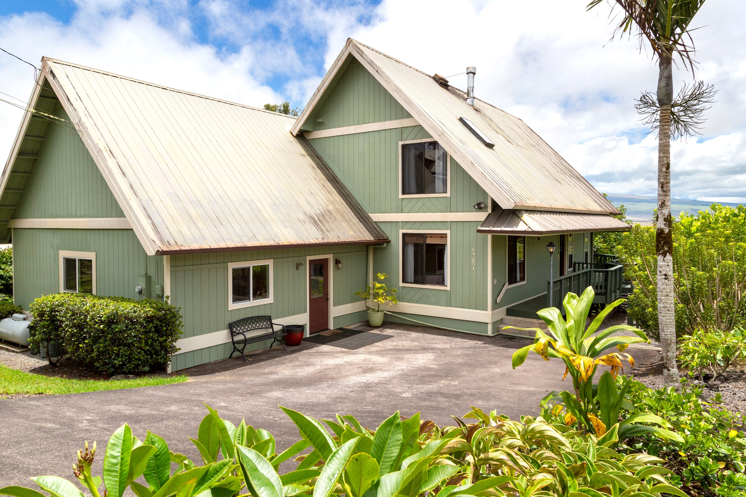 With over 1800sf and an entire wall of windows looking out over a beautiful backyard to Mauna Kea, this home has a lot to offer!  As you enter you can't help but notice the view that seems to be framed like a piece of art across one whole side of the house.  The open concept living/dining/kitchen area is connected to the outside through the slider leading to a wrap-around lanai where you can sit and pick avocados right off the tree.  The ground level of the home has 2 bedrooms and a bathroom down the hall from the living area.  The upper floor of the home is comprised of 625sf and houses the loft space which has incredible views and could be used for many different purposes.  It is currently set up as a home office.  The master suite is located just off the loft area and it boasts high ceilings, a walk-in closet and master bathroom.  There is plenty of storage and extra space in this wonderful home on the hill.  <br><br>The exterior of the home has a nice wrap-around lanai, a storage shed, easy access to the underside of the structure, an on-demand/tankless hot water heater, and a yard full of ornamental plants, fruit trees, and other edibles.  The yard has been very well maintained.