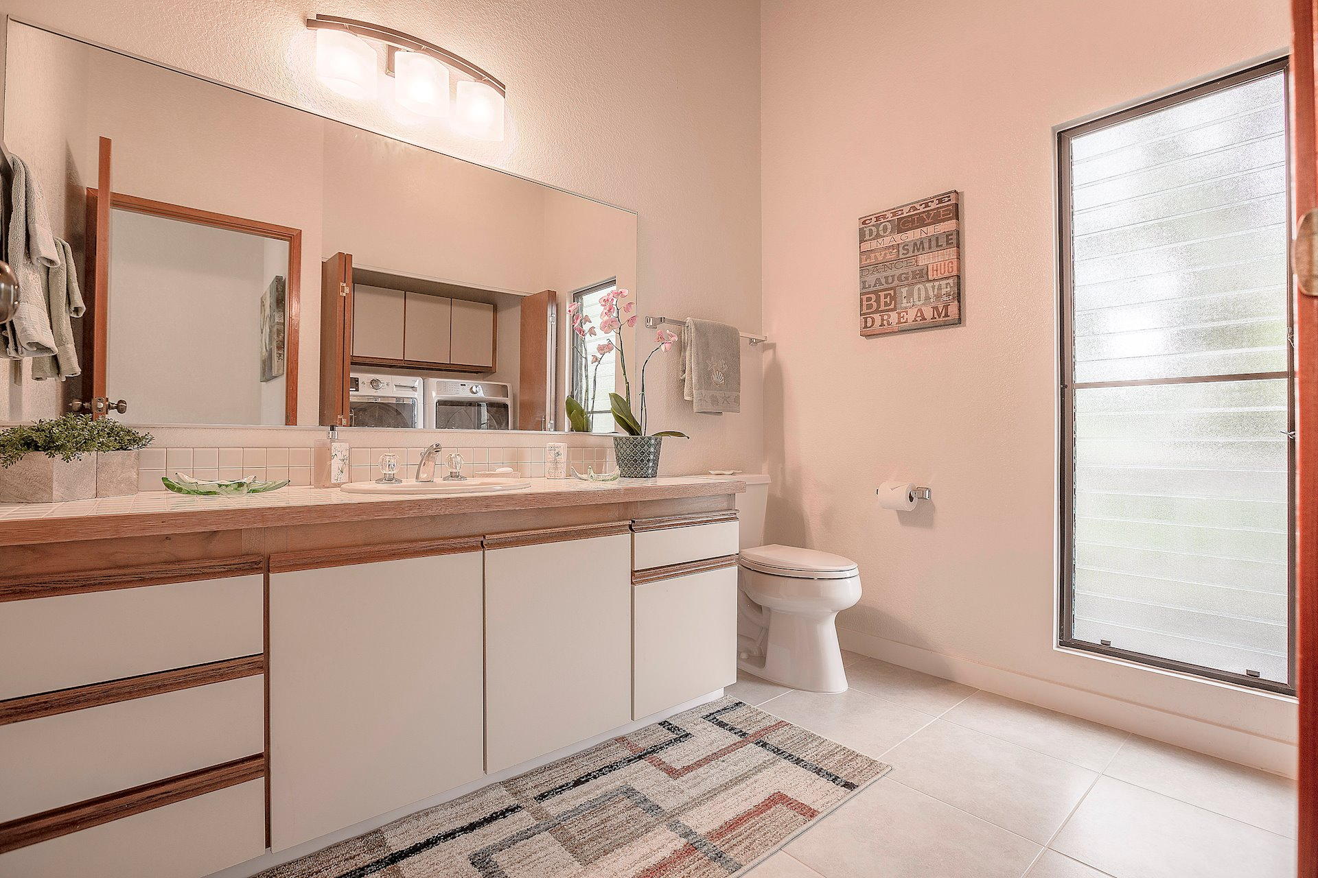Half bath located upstairs, acting as the powder room, guest bathroom and also home to the newer washer/dryer.