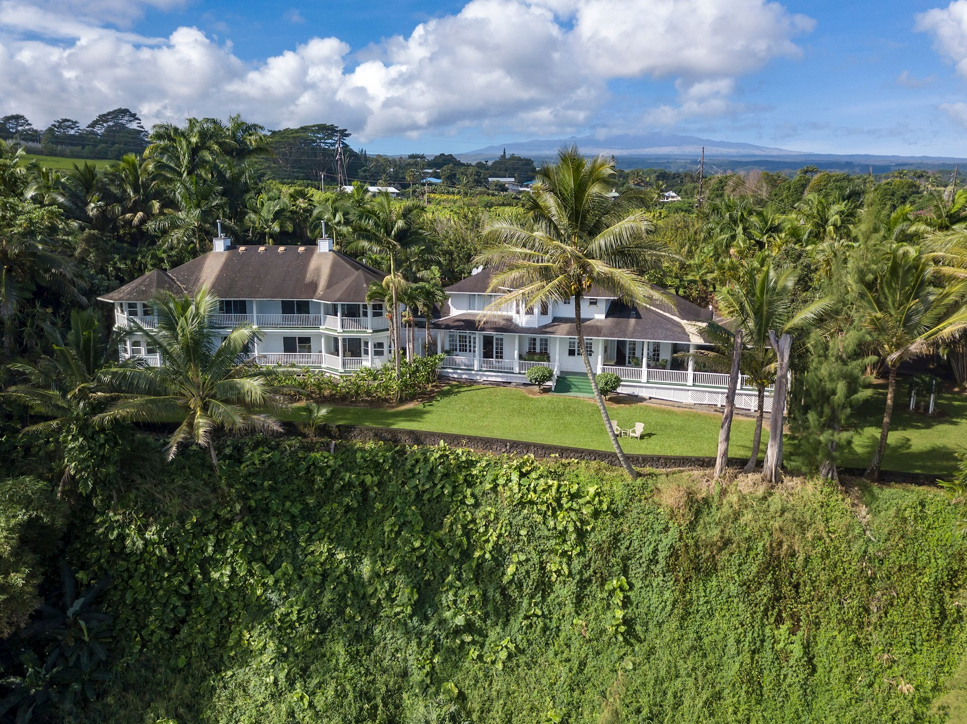 "A most rare 3.40-acre oceanfront residential estate sitting atop a 100-foot cliff is now offered for sale in the Honomu area of the Hamakua Coast on the Big Island of Hawaii. Even more rare is the over 7,200 sqft. of living space, 13 bedrooms and 10.5 bathrooms, huge oceanfront old-fashioned verandas for family, private or public gatherings and with other oceanfront lanais attached to many of the bedroom suites. Ten of the 12 bedrooms face the ocean.  One of the bedrooms is currently being used as an office however it feels more like a library with wood shelving throughout; very special. Visions of the Great Gatsby era with lawn tennis, bird-watching, children playing, parties and croquet suit the style and feel of the home.  Approximately 13 miles to Hilo; 30 to historic Waimea and two miles to Kolekole State Park and world renown Akaka Falls.  Two oceanfront dining areas; one more formal for large gatherings or another as a smaller breakfast room off the huge kitchen.   Conventional electricity, private well water with a reliable history, easy access off main highway. Architecturally speaking the property has resonating Plantation, Victorian and Old Hawaii era qualities.  A distinctly cultivated palm lined driveway, secluded tropical landscaped grounds, seasonal whale and spinner dolphin watching nearly year-long, this property is ready for the market. Seller has worked 2+ years towards preparing their home for sale: new look including flooring, paint, minimalized furniture, expanded maintenance to all parts of the property and a new nursery in order to present and sale as a large yet traditional single-family residence.  Ocean views look to Pohakunanu Bay and locally known surfing sites called ""Ladders"" and ""23 Flats"".  2016 appraisal is above the current list price. Currently operating as the Palms Cliff House B&B, Sellers will consider a sale of the business w/an acceptable offer for the real estate or, at an additional cost with a purchase of the real estate."