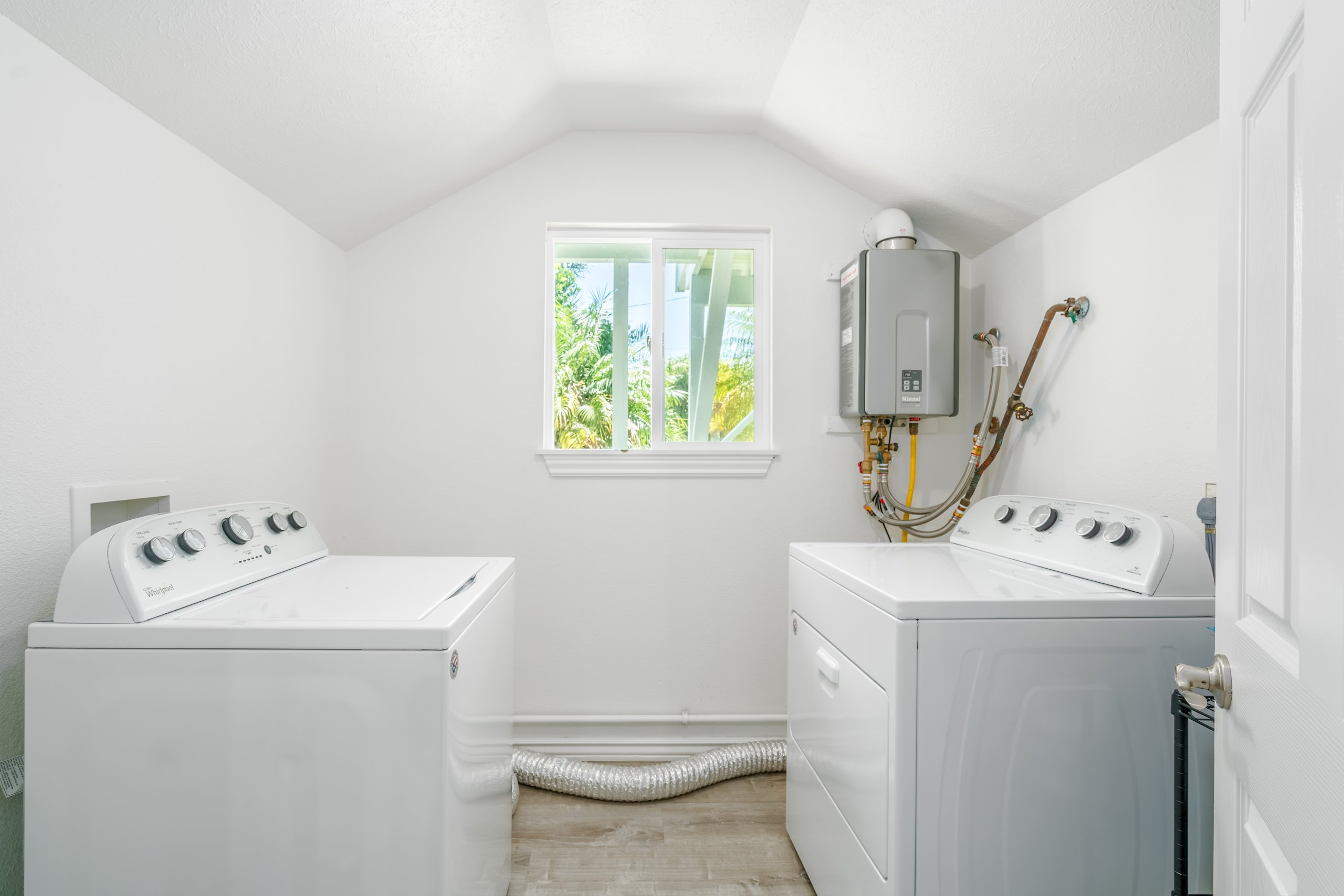 Laundry room downstairs featuring brand new washer/dryer, and on-demand tankless water heater (tanks are right outside)
