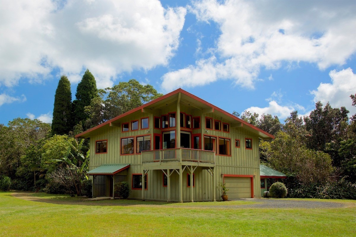 This property with two architecturally unique homes on three acres in lush, historic Volcano Village is available for the first time ever. The gated estate property has two separate legally permitted homes totaling approximately 3660 square feet.  <br>The secluded main home is 2544 sqft. and sited in a Ohia forest with 3 bedrooms, 2 full bathrooms, 2 half baths, a wine cellar, library/office, a two-car garage and indoor pool/spa with an underwater treadmill; pool house is connected by a covered walkway. The main house sited for privacy from the cottage is on the back part of the parcel and includes an open beamed second floor living area and a master suite with a private covered lanai. The central open floor plan includes the kitchen, dining area, living room with fireplace, more lanai, floor to ceiling windows and a powder room. The 2/2 cottage of 1112 sqft. is charming and sits in a forest of hapuu ferns, ginger and mango with tons of glass for natural light.  Included at the cottage is a detached family room, wood decking lanais, a detached artist's studio, a 'treehouse' office and covered walkways leading to the one car garage. The cottage has recently been remodeled with new full kitchen, flooring, general upgrades, paint and repairs.  Both homes are heated and have full photo voltaic systems- 16 panels at the cottage and 12 panels at main home—individual catchment tanks, and their own electric meters.  There are also two greenhouses at the main house.This property offers the option of rental income or for use as a family compound to escape to historic and culturally rich Volcano Village, the Volcano National Park for hiking and exploring, weekly Farmers' Market and farm to table dining experiences.  The Village is also a haven to artists and colorful residents, fabulous B&B's, bird watching, golf, rare native rainforests and botanical abundance.