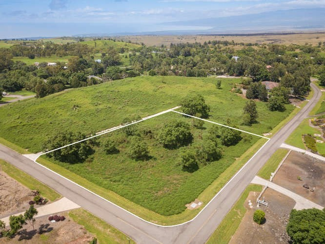 Incredible opportunity to build your dream home on this 1+ acre corner lot located in the gated equestrian community of Puu Lani Ranch. Located at the perfect elevation of approx. 2,000+ feet, Puu Lani lots and homes are situated on a minimum of one acre. Facilities include a clubhouse, equestrian center, tennis courts, walking and horse riding trails, and workout center. Enjoy the views of Mauna Kea, Mauna Loa, Hualalai, and Haleakala, as well as Puu Waa Waa cinder cone throughout this beautiful neighborhood. Surrounded by thousands of acres of state preserve land, and adjacent to Makani Golf Club (formerly Big Island Country Club), Puu Lani Ranch has something for everyone.  PLEASE NOTE: Membership to the member owned/non-profit water company and connection fee for this lot is already paid for and current! (Current value of this is approximately $12,000) Please visit www.NapuuWater.com for more info. The paved strip shown in the photos is located on the adjacent lot.