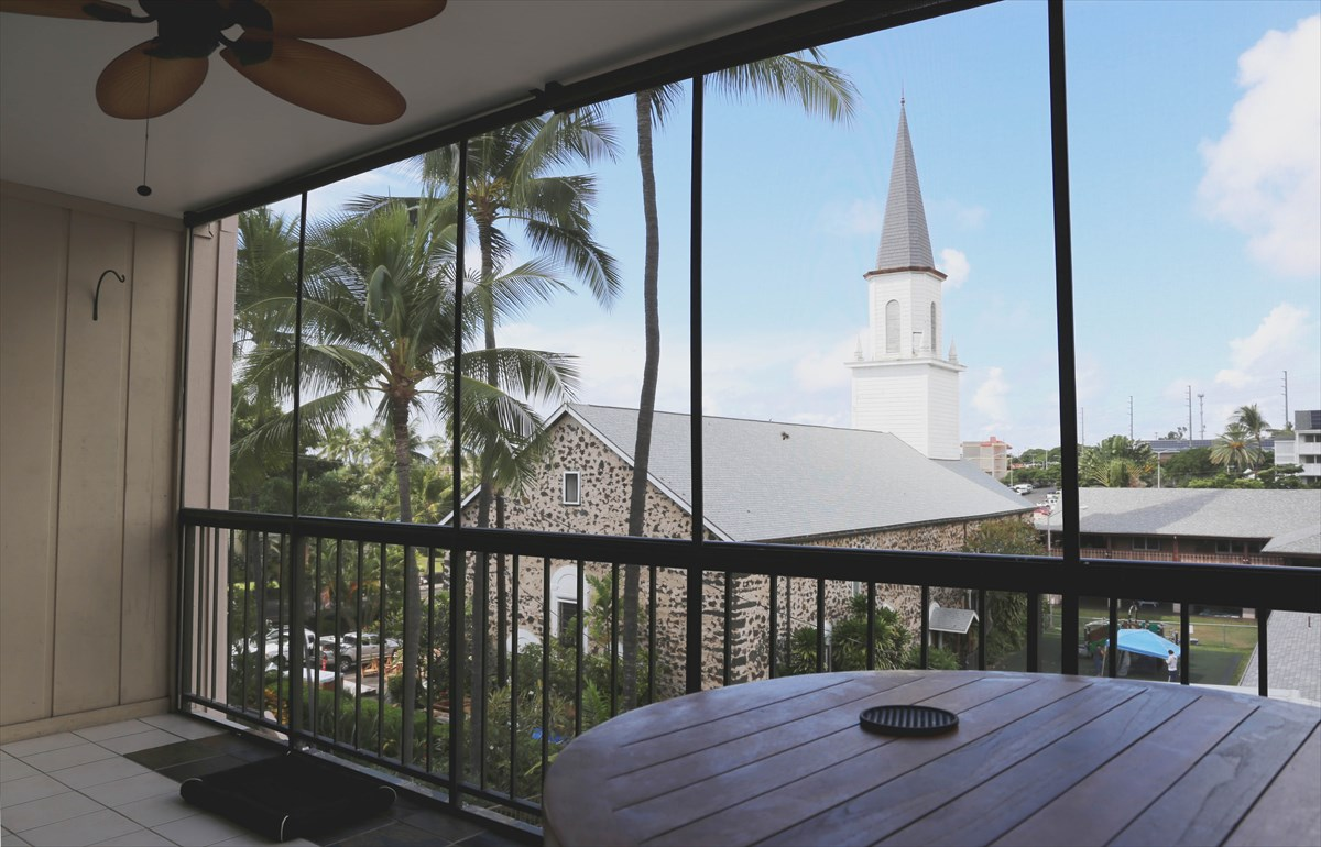 This light, bright and airy condo features a spectacular display of historic Mokuaikaua Church. It is located in the heart of Kona. The 1-bedroom 1-bath home has a living room that opens up to a spacious screened-in lanai. The kitchen has upgraded features and appliances, including double ovens. The bathroom is nicely upgraded with new vanity and a beautifully tiled walk-in shower. The bedroom has wall to wall mirrored closet doors and comes with a wall-mounted smart TV. There is plenty of storage that can be found throughout the home, with an additional dedicated storage unit on the upper floor.<br>Kona Plaza amenities and services include a pool, parking in a secured underground garage, solar electricity, water, cable TV, trash removal, and landscaping.